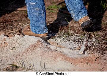 Man walking through a pile of sawdust