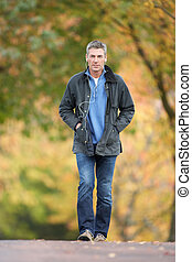 Man Walking Through Autumn Park Listening to MP3 Player