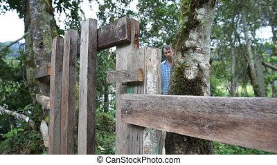 Man Walking Through Gate Coming