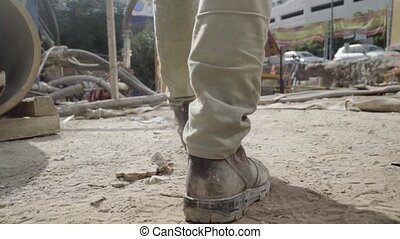 Man walking through working industrial site. Follow shot to a male worker feet in boots. engineering Legs of young man stepping on stones and cables Low angle view Close up Slow motion