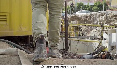 Man walking through working industrial site. Follow shot to a male worker feet in boots. engineering Legs of young man stepping on hose and cables Low angle view Close up Slow motion