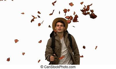 Man walking under leaves falling on