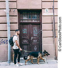 man walking with a dog on the street