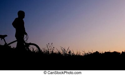 man walking with bicycle against sunset sky