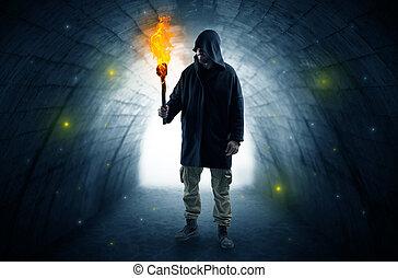 Man walking with burning flambeau in a dark tunnel