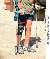 Man walking with crutches, rehabilitation after injury