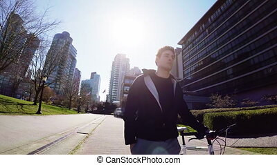 Man walking with his bicycle in the city 4k - Man walking...