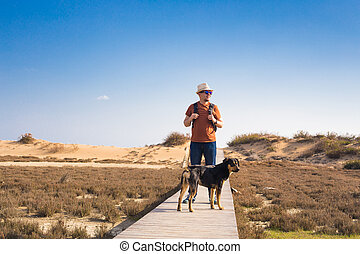 Man walking with his dog on a road leading through beautiful landscape