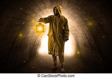 Man walking with lantern in a dark tunnel