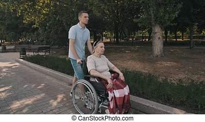 Man walking with old woman on a wheelchair