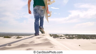 Man walking with sand board in the desert 4k - Rear view of...