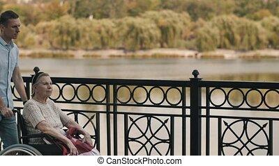 Man pushing senior woman in a wheelchair at the park