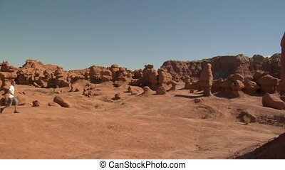 man walks across landscape goblin Valley Utah
