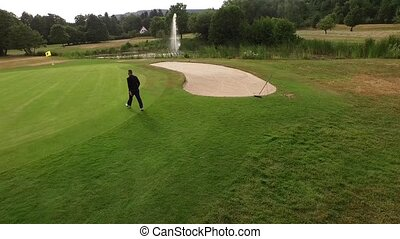 man walks across the golf course next to a sand trap