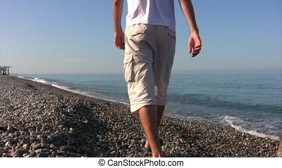 man walks along coast and looks at sea