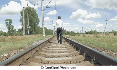 Man walks along railway tracks in the countryside