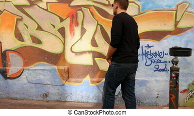 man walks and leans against wall