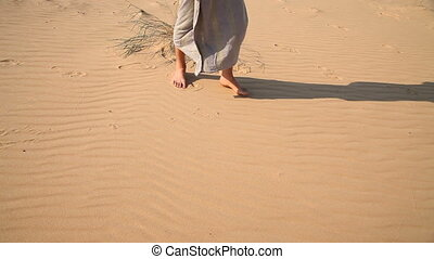 Man walks barefoot through the desert