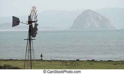 Man Walks Dog Pacific Coast Beach Butte Windmill - Windmill...