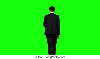 Man walks down the street, puts his hand in his pocket and waves. Green screen. Back view