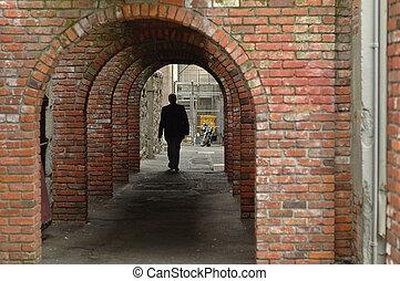 man walks in a brick tunnel