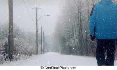 Man in winter clothing walks along road near trees in snowstorm
