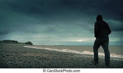 Man walking on stormy beach in the evening