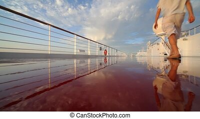man walks on wet deck of cruise ship
