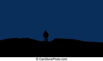 Man Walks Over Hill At Night