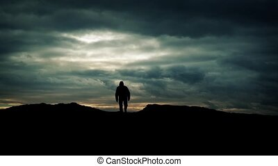 Man Walks Over Hill On Dramatic Sky Silhouette