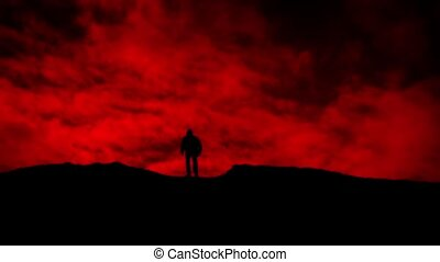 Man Walks Over Hill On Red Sky Silhouette