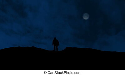 Man Walks Over Hill With Moon Above