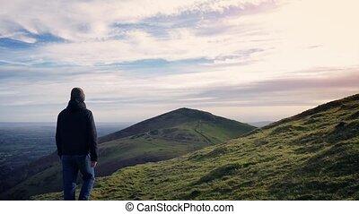 Man Walks Over Hilltop At Sunset
