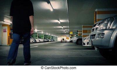 Man Walks To Car In Parking Garage
