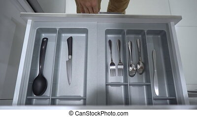 man walks to the kitchen cupboard and takes a spoon and fork...