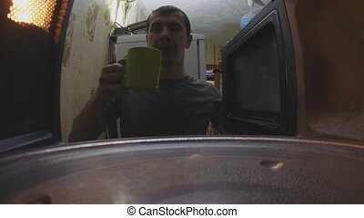 man warms coffee in microwave lifestyle oven first-person...