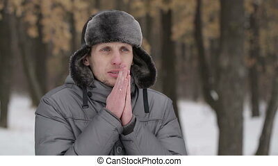 Man warms hands in winter