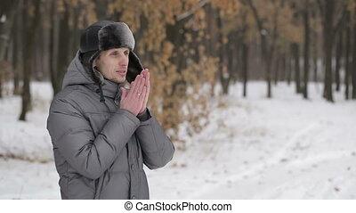 Man warms hands in winter