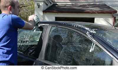 man wash car roof sponge - Man with sponge wash automobile...