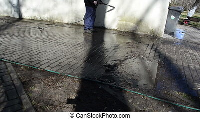 worker with a strong jet of water cleans the dirt white garage wall.
