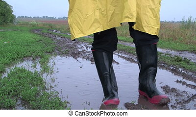 Man washes away the dirt from rubber boots in puddle on country road