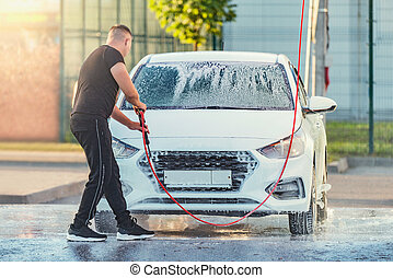 Man washes his car on the open air.
