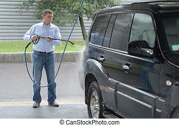 man washes his car