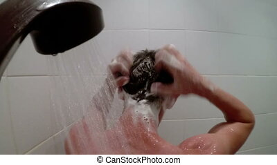 Man washes his head in the shower - A man washes his head in...