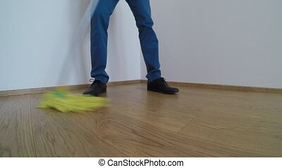 Man washes the parquet floor with the yellow mop - Man...