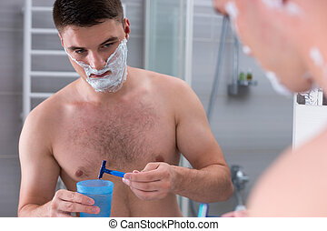 Man washing a razor in the cup with water