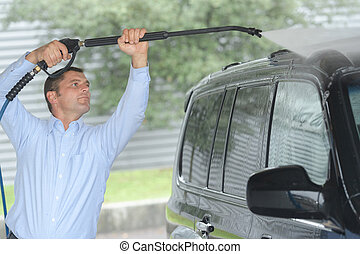 man washing car with high pressure spray