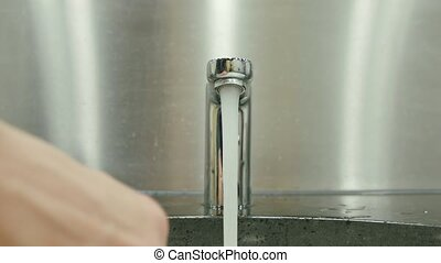 Man Washing Hands in the Bathroom - A man washing hands in a...