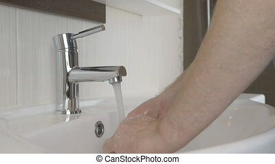 Man washing hands in the bathroom of the hotel