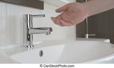Man washing hands in the bathroom